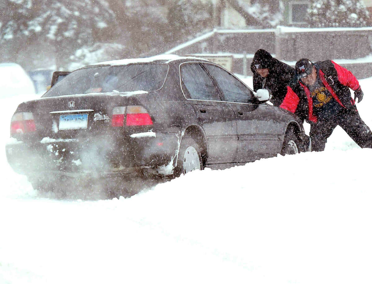 (Peter Hvizdak - New Haven Register) Good Samaritan's help push a car stuck in the snow on Middletown Avenue in New Haven during the Nor'easter snow storm Thursday, February 9, 2017.