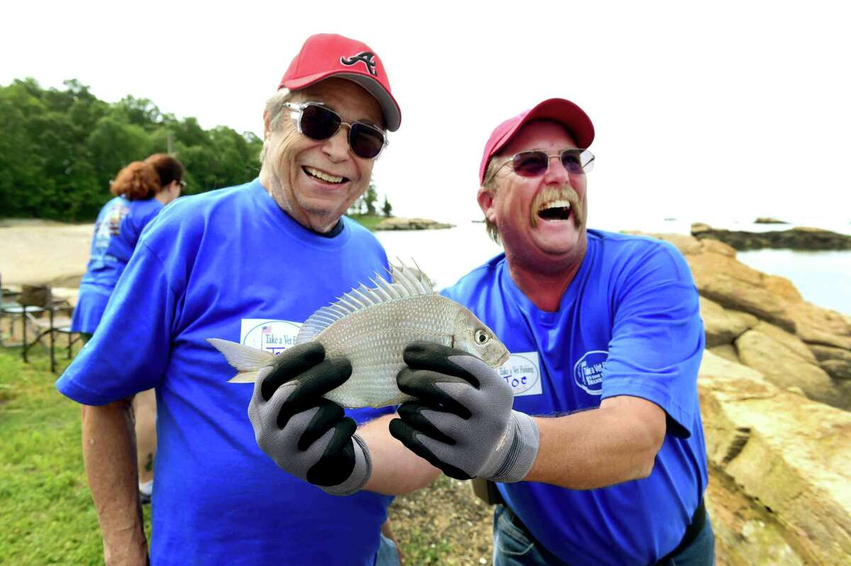 (Peter Hvizdak - New Haven Register) Jon Staski, left, A. U.S. Navy Vietnam War veteran, left, shows off his catch with volunteer Joe Aronson of Middlebury during the First Congregational Church of Branford 10th annual Take-A-Vet Fishing event at Killiam's Point in Branford Thursday morning, June 23, 2016 with Veterans from the West Haven VA Blind Center.
