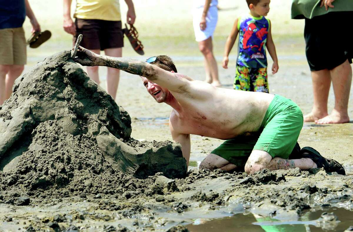(Peter Hvizdak - New Haven Register) Ron Warzel, of Milford pays attention to details as he creates a Viking Ship with and Odin bowsprit during the Milford Arts Council annual sand Sculpture contest on Walnut Beach in Milford Saturday, July 30, 2016.