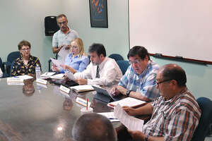 Our Laredo representative, Vish Viswanath, standing, distributes copies of his presentation to Old Mercy Hospital Bldg. Ad-Hoc Committee members met, Tuesday, August 1, 2017, at the City of Laredo Environmental Services Department Conference Room to discuss the future of the building which has been abandoned for 17 years.