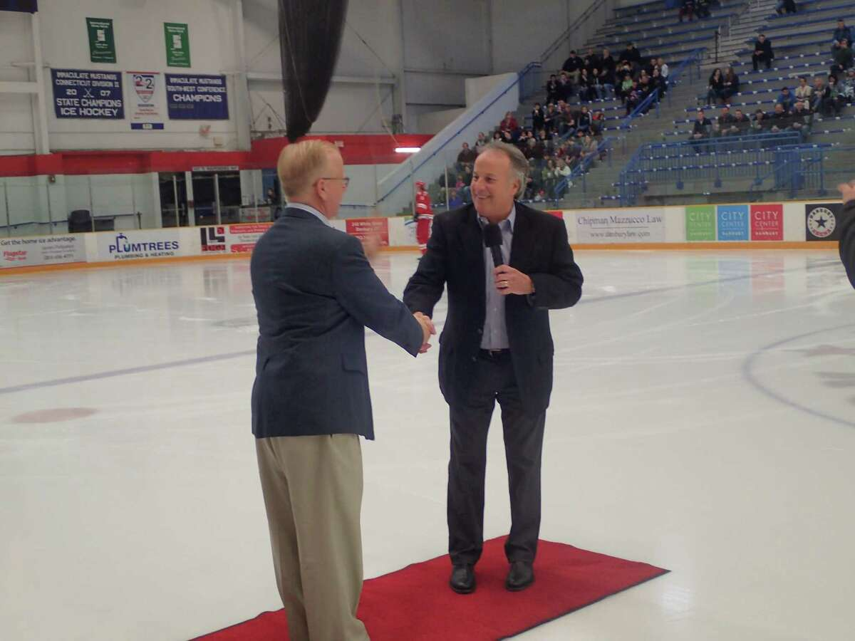 Danbury Titans owner Bruce Bennett, right, shakes hands with Danbury Mayor Mark Boughton during a pregame awards ceremony prior to the Federal Hockey League game between the Titans and the Brewster Bulldogs at the Danbury Arena March 26, 2016. Boughton received an FHL Founders Award.