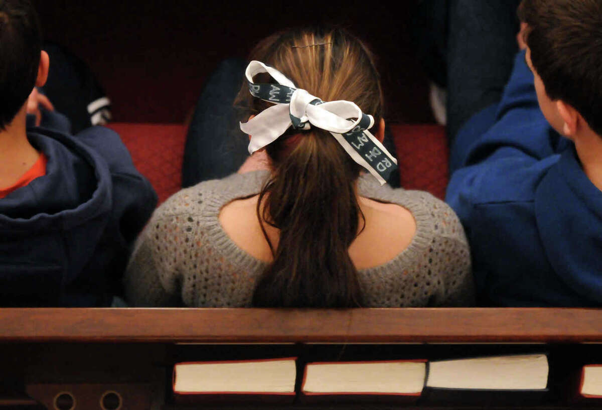 Newtown Congregational Church held a Service of Hope and Healing. An attendee wears a ribbon with the initials of the slain children. Mara Lavitt/New Haven Register 1/20/13