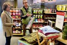 (Peter Hvizdak - New Haven Register) Customer Caroline Burns of Ridgefield, left, with Mason Trumble, REI marketing coordinator, discuss products at the REI retail chain store specializing in outdoor recreational equipment, outdoor clothes, footwear and travel gear that recently opened a store in Orange. Tuesday, December 19, 2016.