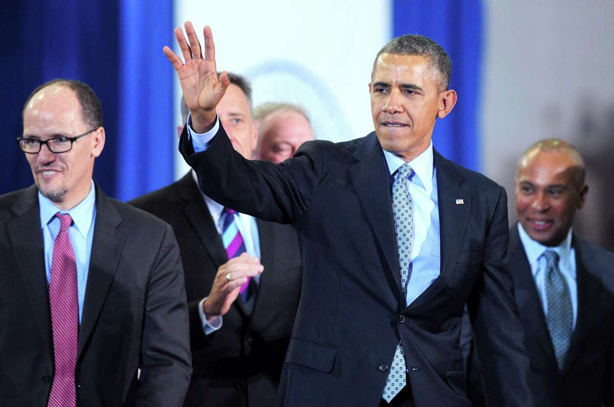 President Barack Obama waves to the crowd after giving a speech about raising the minimum wage at Central Connecticut State University in New Britain on 3/5/2014. At left is the U.S. Secretary of Labor Thomas Perez and at right is Massachusetts Governor Deval Patrick. Photo by Arnold Gold/New Haven Register