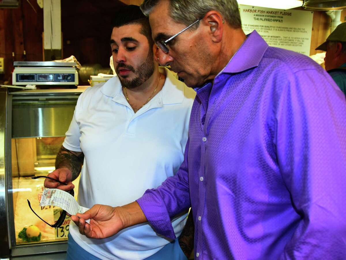 Michael Mastrantuono, left, executive chef of the restaurant 15 Church in Saratoga Springs, looks at the bill for fish he just bought for the restaurant with 15 Church co-owner Paul McCullough at Harbor Fish Market in Portland, Maine, on Tuesday, Aug. 1, 2017. The pair flew to Portland for lunch and a trip to the fish market with thoroughbred owner and 15 Church customer Lee Pokoik on Pokoik's private plane. (Photo by Steve Barnes/Times Union.)