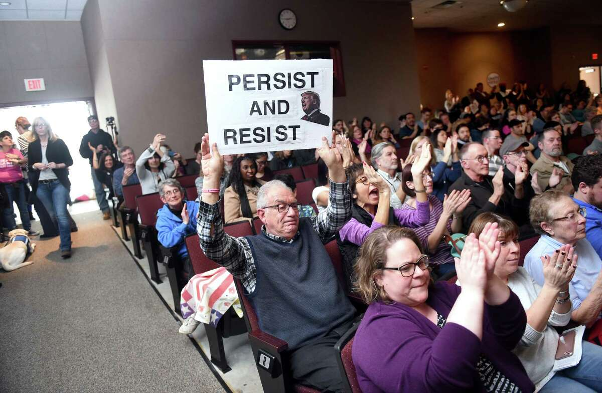 Peter Bunzl (center) of Oxford displays a sign opposing President Donald Trump during a Town Hall meeting with U.S. Senator Richard Blumenthal at Wilbur Cross High School in New Haven on 2/25/2017. Photo by Arnold Gold/New Haven Register agold@newhavenregister.com