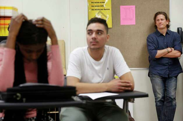 """Matthew Russell, right, stands in the back during a poetry lesson at Middle College. When asked why he always stands in the back, Russell says, """"You ask me why I don't stand in the center of that? Please. It's like eclipsing the sun, right? Like? How am I supposed to eclipse the sun? It doesn't matter if I stand in the center of it, you won't see me anyway."""" Photo: Jon Shapley, Houston Chronicle / © 2017 Houston Chronicle"""