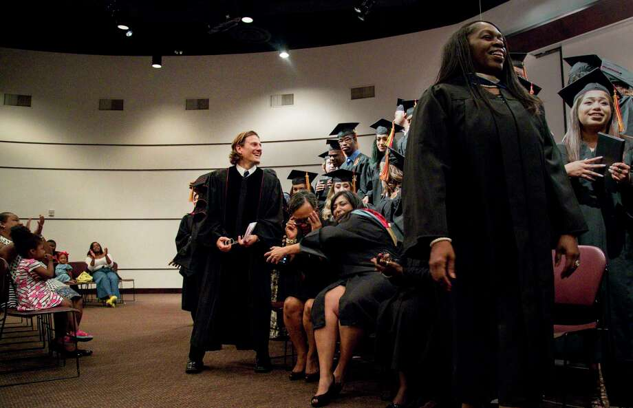 Matthew Russell, center, smiles after a graduation ceremony for Middle College High School. He was the spring 2017 commencement speaker, after building a relationship with staff and students through his Iconoclast poetry program. Photo: Jon Shapley, Houston Chronicle / © 2017 Houston Chronicle