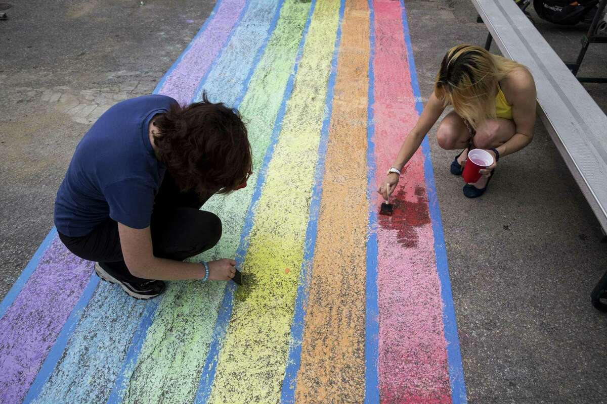 Volunteers Michelle Cowan (left) and Alize Sanchez use chalk to create a rainbow crosswalk last month at the intersection of Evergreen Street and Main Avenue. The city's Governance Committee on Wednesday unanimously passed a proposal to permanently paint a rainbow crosswalk on Main Avenue in recognition of San Antonio's commitment to the LGBT community.