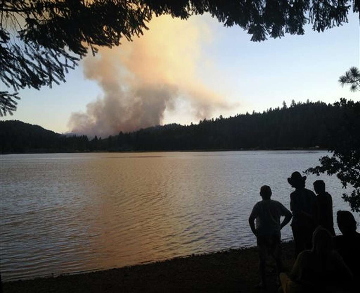 In Oregon, people gather on the shores of Lake Selmac on July 28, 2014 to watch the Reeves Creek fire. Since then, Oregon expenditures for wildfire prevention and recovery have skyrocketed as the state is now categorized as abnormally dry by the NIDIS in regions like Portland Metro, Willamette Valley and North Coast, and the northern region of Central Oregon.