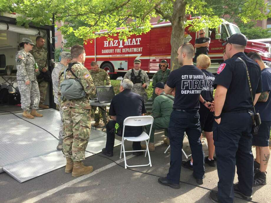 Members of the Danbury Fire Department, EMS and National Guard discuss a training exercise held August 2, 2017, at Western Connecticut State University. Photo: / Contributed
