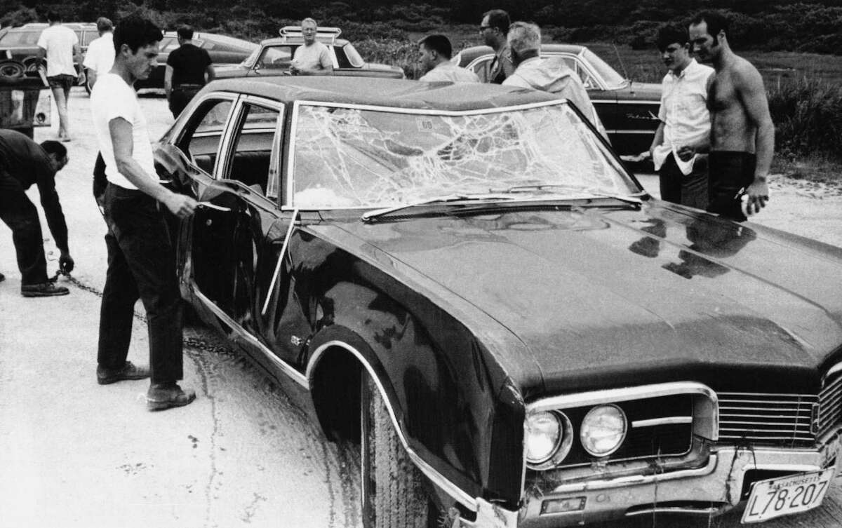 Onlookers inspect Sen. Edward Ted Kennedy's car after it was hauled on July 19, 1969 in Edgartown, from water with body of Mary J. Kopechne in the rear seat. The 38-year-old Massachusetts Democrat is expected to face public questioning abouth Kopechne's death for the first time in the inquest that opens in Edgartown, Mass., (AP Photo)