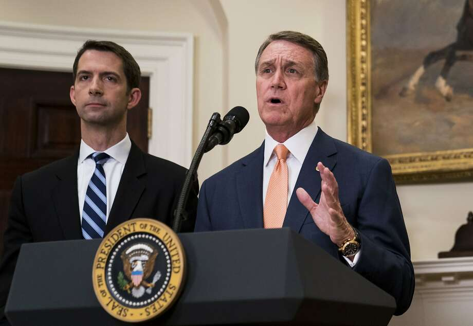 Sens. Tom Cotton (R-Ark.) and David Perdue (R-Ga.) deliver a statement after President Donald Trump announced proposed immigration legislation at the White House, in Washington, Aug. 2, 2017. The Raise Act, sponsored by Cotton and Perdue would overhaul decades of immigration policy by replacing a system that favors family ties in deciding who can move to the United States legally with merit-based preferences based on skills and employability. (Doug Mills/The New York Times) Photo: DOUG MILLS, NYT