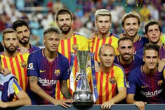 Neymar, tercero desde la izquierda, posa con sus compañeros y el trofeo tras vencer al Real Madrid en un amistoso de pretemporada el sábado 29 de julio de 2017, en Miami Gardens, Florida. Ese partido pudo haber sido el último del astro brasileño con el club catalán, al que le expresó el miércoles su deseo de irse al PSG de Francia. (AP / Lynne Sladky)