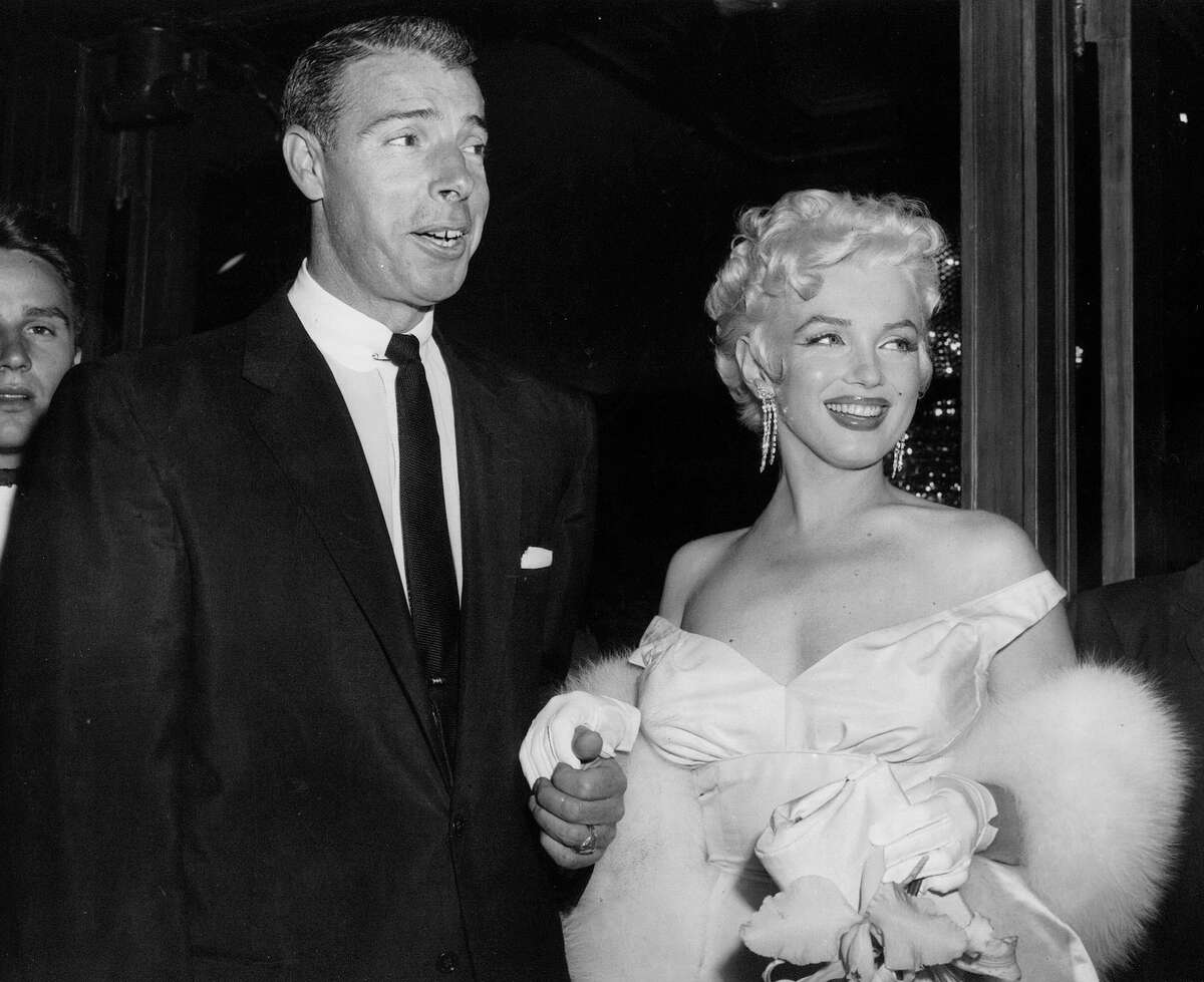 FILE - In this June 2, 1955 file photo, actress Marilyn Monroe, right, dressed in a glamorous evening gown, arrives with Joe DiMaggio at the theater. Monroe's Lost Archives are coming to light now, along with a cache of other Monroe memorabilia that the Beverly Hills auction house Julien's is putting up for sale on Dec. 5-6, 2014. Along with the letters from DiMaggio, Miller and such Hollywood luminaries as Cary Grant and Jane Russell are some of the actress' favorite clothes, photographs, paintings and other keepsakes.