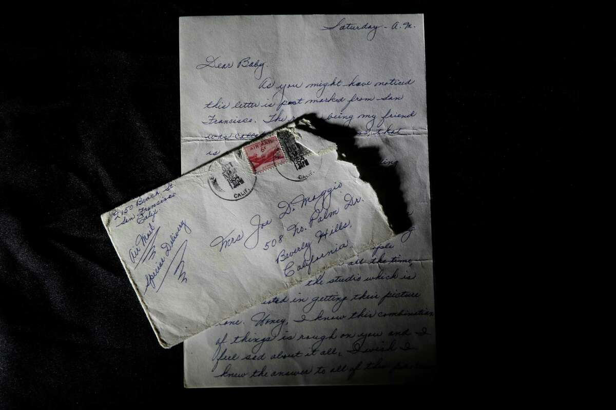 This Friday, Nov. 7, 2014 photo shows part of a three-page handwritten letter and original envelope postmarked Oct. 9, 1954 from baseball legend Joe DiMaggio to Marilyn Monroe on display at Julien's Auctions in Beverly Hills, Calif. The letter is among the 300 items that are part of
