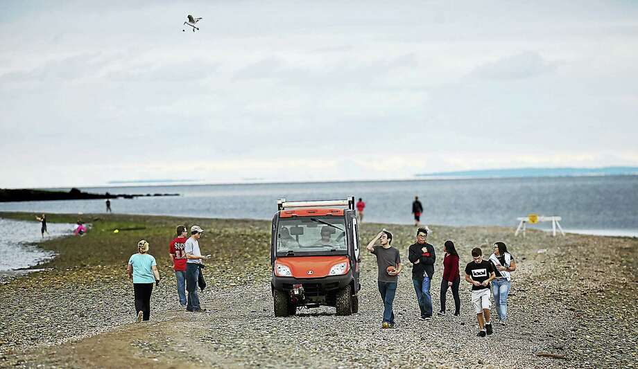 DEEP officers warn beach-goers walking on the sandbar of the strong curtrents and undertow at low-tide at Silver Sands State Park, a public recreation area located on Long Island Sound in Milford, Tuesday, July 25, 2017.. (Catherine Avalone – Hearst Connecticut Media) Photo: Catherine Avalone/New Haven... / Catherine Avalone/New Haven Register
