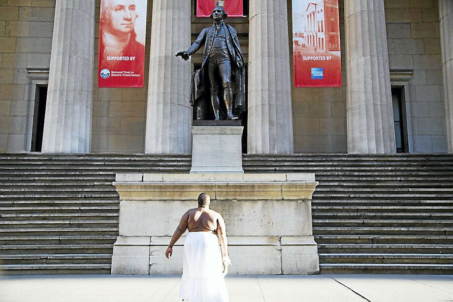 """FAUSTINE AT ARTSPACE: Nona Faustine, who photographs her body, sometimes only partially clothed, at iconic U.S. monuments and sites that carry the invisible histories of African-American enslavement (like here at Federal Hall in New York City), is lead artist of the Summer Apprenticeship Program at Artspace in New Haven. The program (held over three weeks in July) is using Faustine's """"My Country"""" series of photos as a prompt for 15 interns from local high schools to identify sites around New Haven that carry teens' """"invisible stories."""" The exhibition of that work will run July 28-Sept. 9 at 50 Orange St. An awards ceremony will be held July 28 at 5:30 p.m. Photo: Digital First Media"""