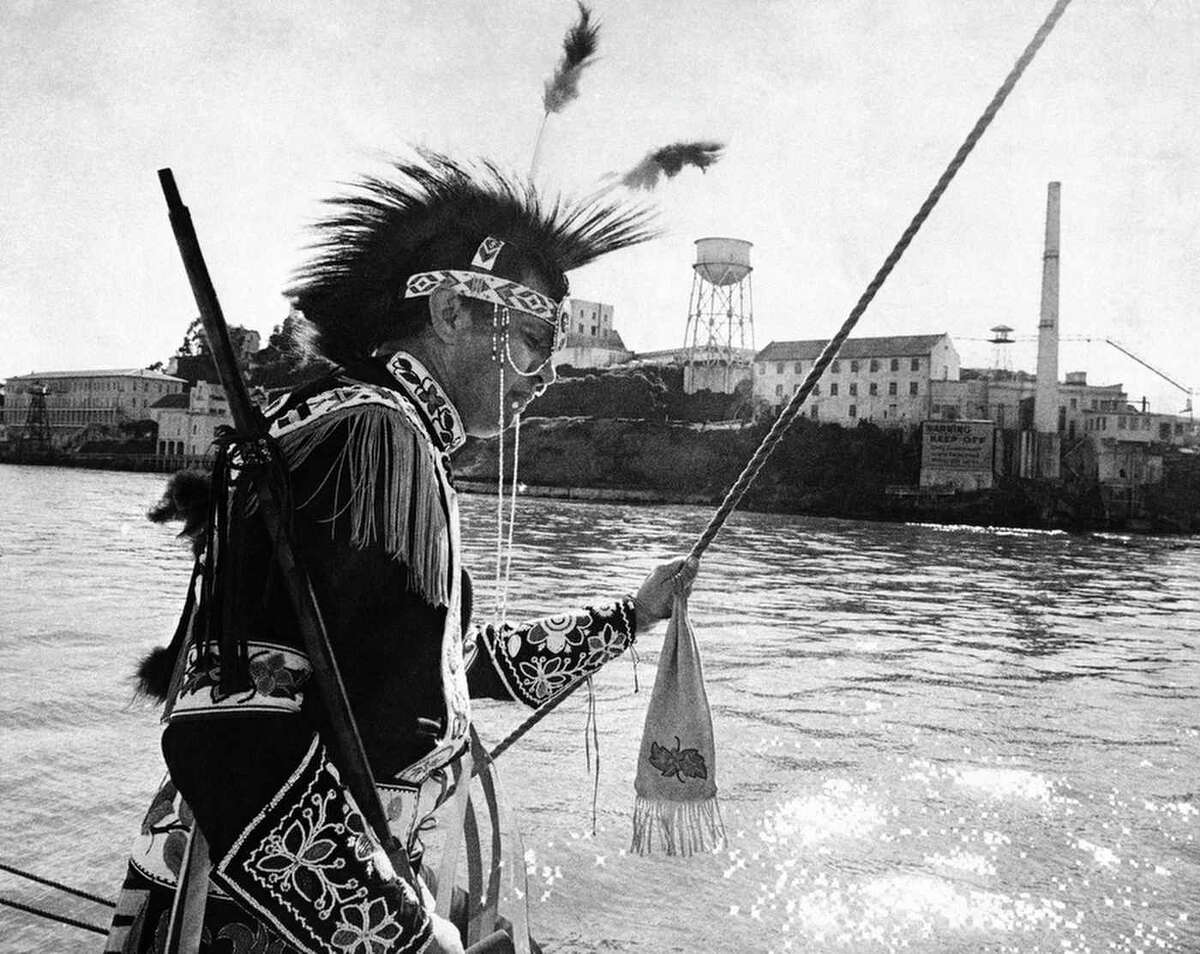 Fie photo of Adam Nordwall, 40, a Chippewa Indian, standing at the rail of the three-masted clipper Monte Cristo as it sailed past Alcatraz Island in San Francisco Bay, Nov. 9, 1969. Nordwall led a group of Indians in a proposal to purchase the Island for $24 in beads and cloth and suggested it be made into an Indian center.