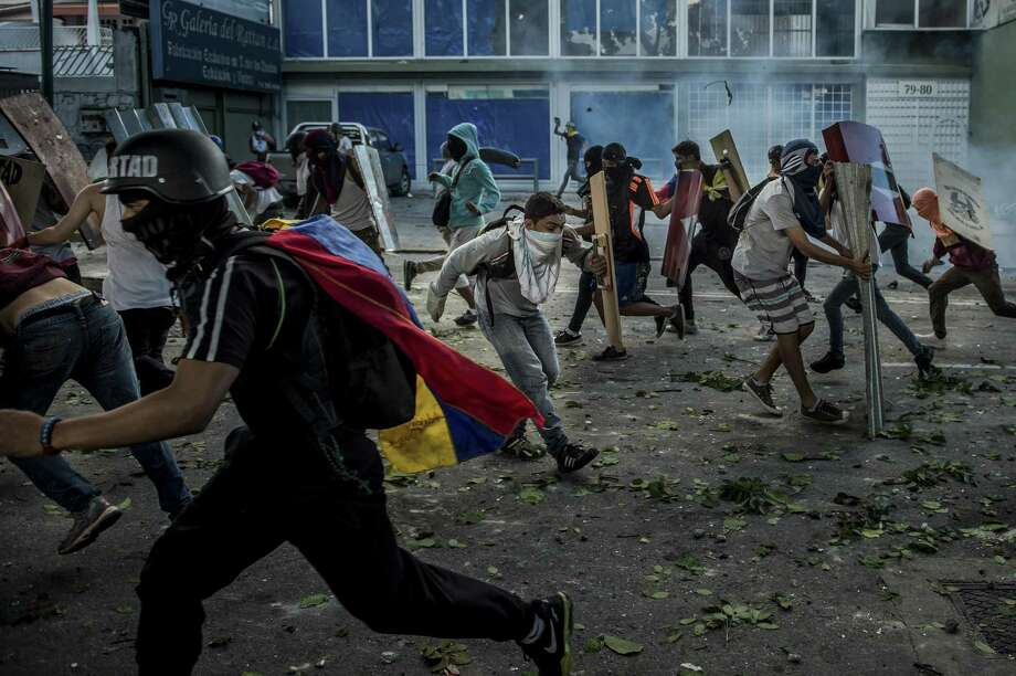 Resistance members clash with soldiers last week. Venezuelans already are hurting under President Nicolás Maduro. U.S. must not add to their suffering. Photo: Meridith Kohut /New York Times / NYTNS