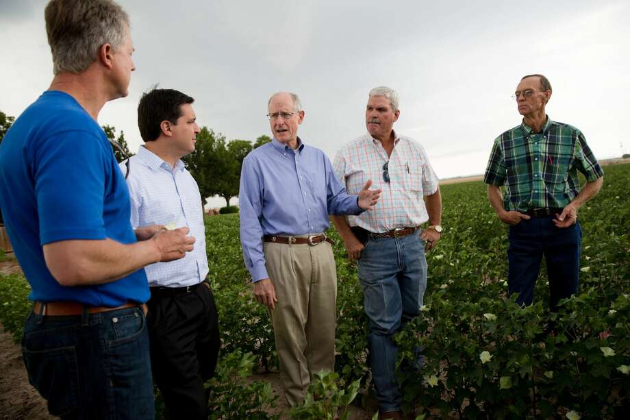 U.S. Rep. Mike Conaway, center, speaks with U.S. Reps. David Rouzer of North Carolina, second from left, and Roger Marshall of Kansas, second from right, and farmers at a cotton farm outside San Angelo on Monday. Photo:  Austin Price/The Texas Tribune