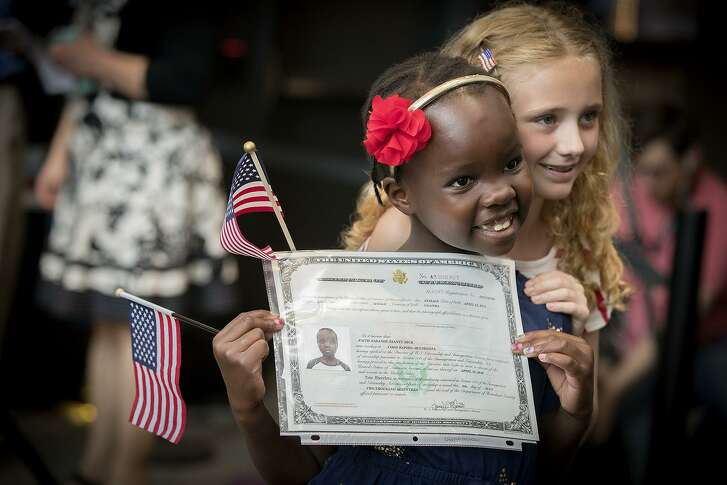 Faith Nasande Ssanyu Mick, 6, from Uganda, got a hug from her sister Ainsley Mick, 8, of Coon Rapids after she received her Certificate of Citizenship during a U.S. Citizenship and Immigration Services citizenship ceremony at the Minnesota Children's Museum, Friday, July 21, 2017 in St. Paul, Minn. (Elizabeth Flores/Star Tribune via AP)