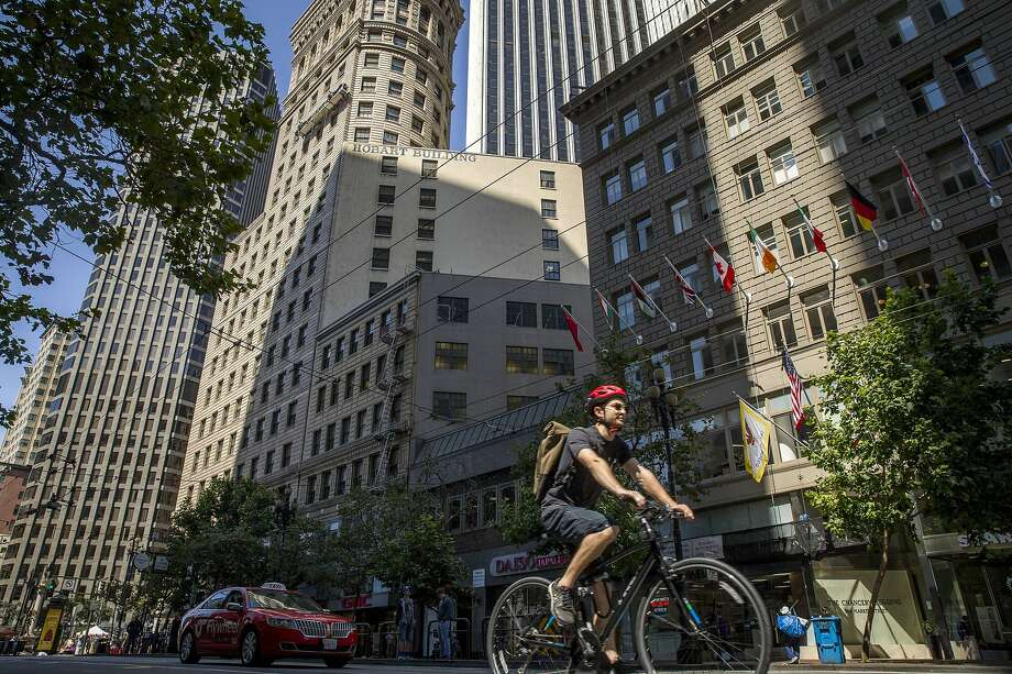 A bicyclist and taxi along Market Street on Wednesday, Aug. 2, 2017, in San Francisco, Calif. A  plan calls to ban cars, including Uber and Lyft, from Market Street�s eastern reaches while delivering continuous protected bike lanes and Muni-only lanes. It would make room for taxis and other commercial vehicles such as delivery trucks. But it would get rid of Market Street�s signature brick sidewalks. Photo: Santiago Mejia, The Chronicle
