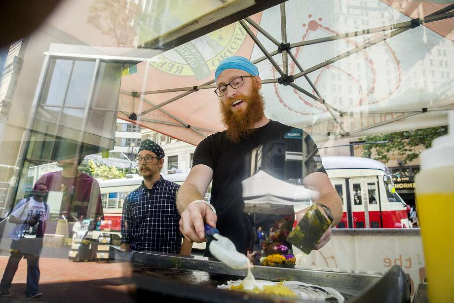Avtar Khalsa (center) makes dosas for a customer at The Dosa Brothers along Market Street on Wednesday, Aug. 2, 2017, in San Francisco, Calif. A  plan calls to ban cars, including Uber and Lyft, from Market StreetÕs eastern reaches while delivering continuous protected bike lanes and Muni-only lanes. It would make room for taxis and other commercial vehicles such as delivery trucks. But it would get rid of Market StreetÕs signature brick sidewalks. Photo: Santiago Mejia, The Chronicle