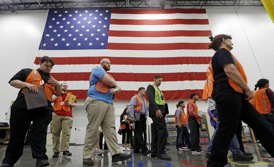 Job applicants walk past an American flag at an Amazon recruiting event in Kent, Wash., on Aug. 2. Photo: Elaine Thompson, Associated Press
