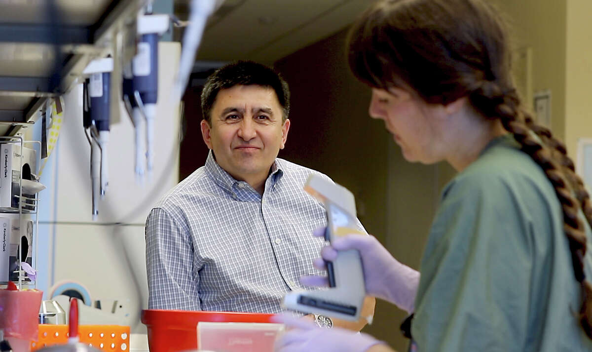 In this photo provided by Oregon Health & Science University, taken July 31, 2017, Shoukhrat Mitalipov, left, talks with research assistant Hayley Darby in the Mitalipov Lab at OHSU in Portland, Ore. Mitalipov led a research team that, for the first time, used gene editing to repair a disease-causing mutation in human embryos, laboratory experiments that might one day help prevent inherited diseases from being passed to future generations. (Kristyna Wentz-Graff/Oregon Health & Science University via AP)