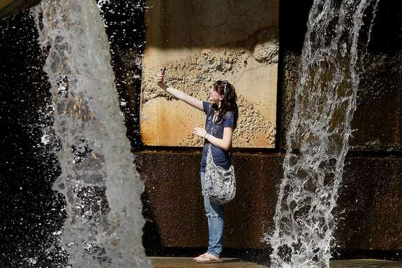 Ellie Koning of Newark, Calif. stopped to take her own picture inside the Vaillancourt fountain at Justin Herman Plaza. Summer finally came to San Francisco, Calif. Monday September 19, 2011.