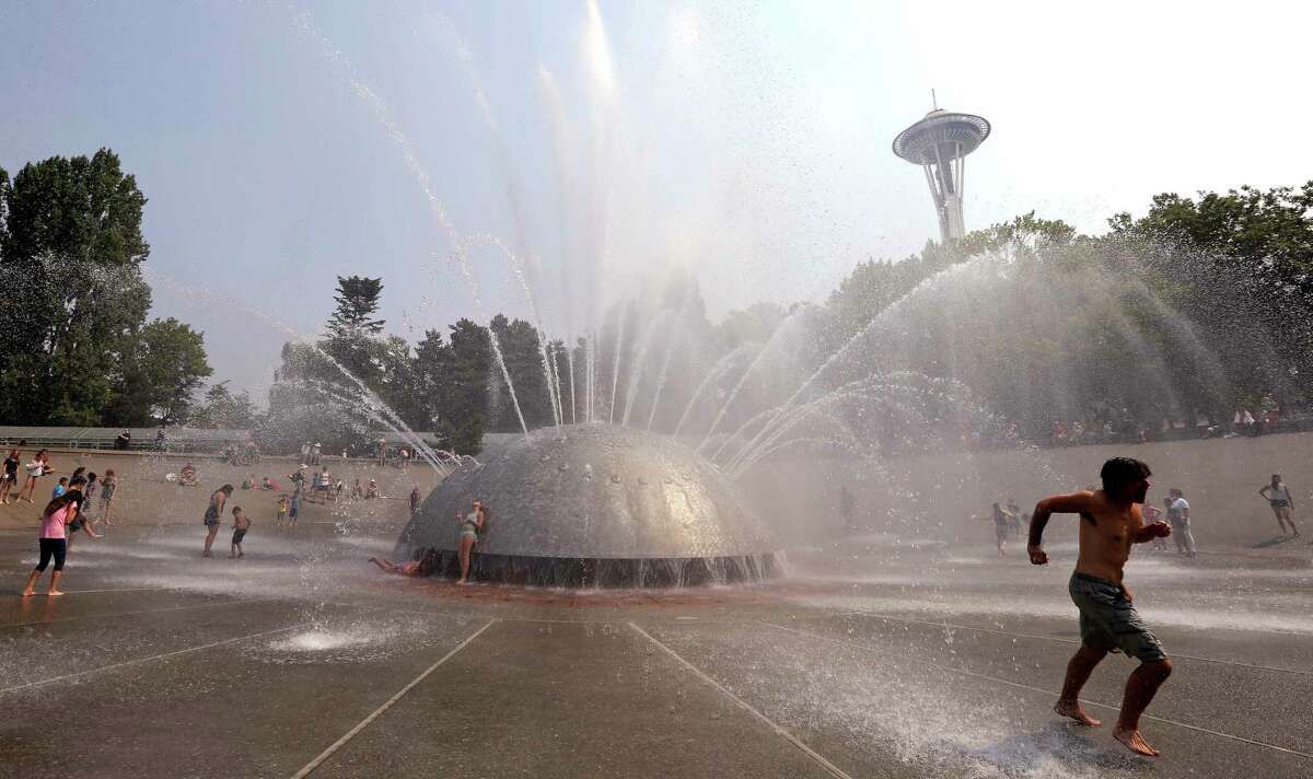 A man races away as a jet begins to spray toward him at the International Fountain at the Seattle Center during a heat wave Wednesday, Aug. 2, 2017, in Seattle. An excessive heat warning for the area continues through Friday evening, as unusually hot weather will bring temperatures nearing a peak of 100 degrees on Thursday.
