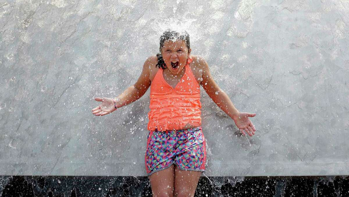 A child reacts to water pouring over her as she stands in the International Fountain at the Seattle Center during a heat wave Wednesday, Aug. 2, 2017, in Seattle. An excessive heat warning for the area continues through Friday evening, as unusually hot weather will bring temperatures nearing a peak of 100 degrees on Thursday.