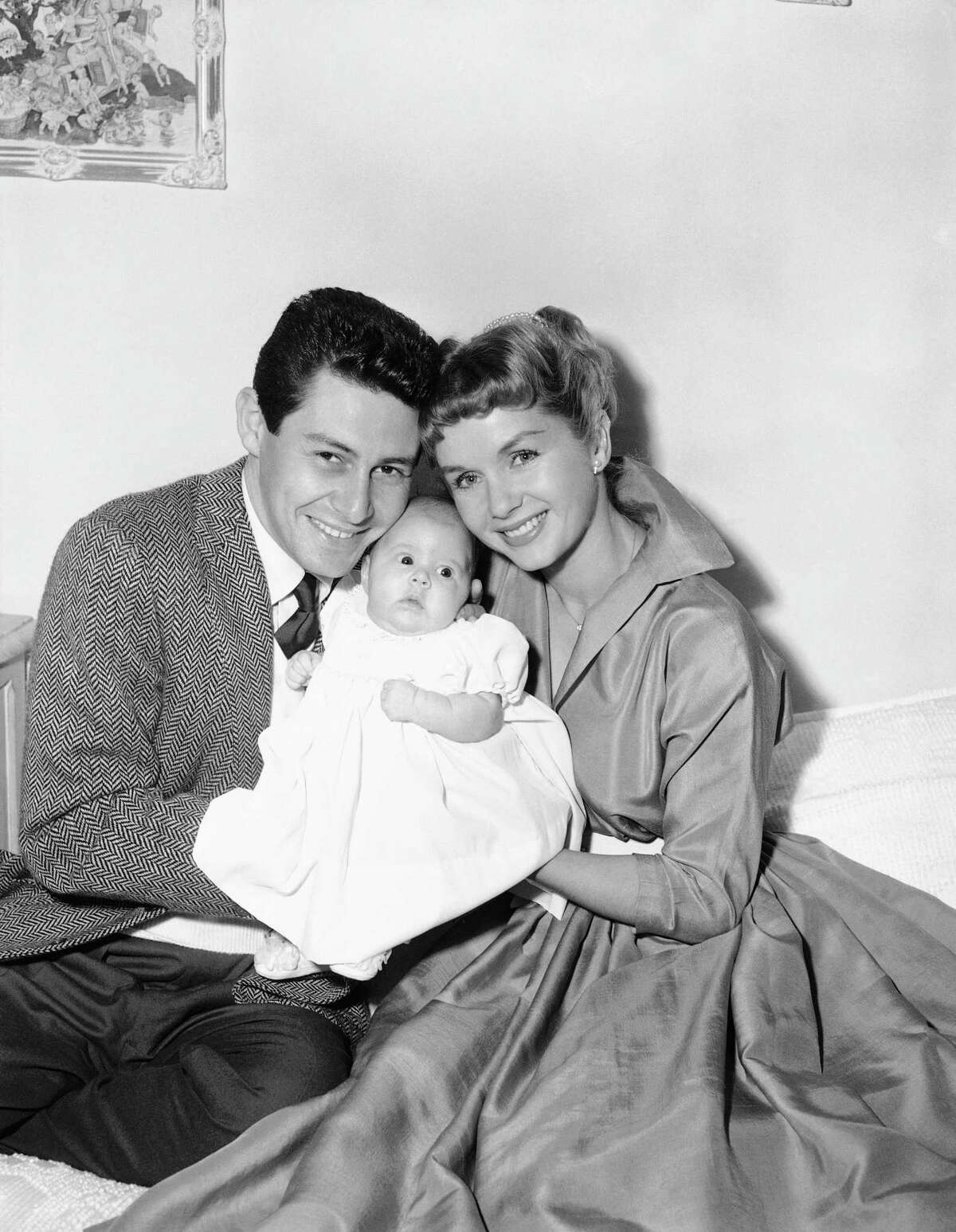 Eddie Fisher and Debbie Reynolds appear before the camera in their real roles of happy parents as they and their young daughter, Carrie Frances Fisher, pose for their first family group picture, in Hollywood, Jan. 2, 1957. Carrie Frances was born Oct.21, 1956. The young stars, appropriately, are appearing in a film titled