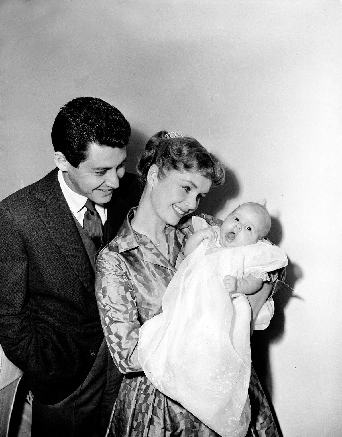 Actress Debbie Reynolds and her husband, singer Eddie Fisher, pose with their ten-week-old daughter Carrie Frances for the first family picture, January 2, 1957, in Hollywood, California. (AP Photo)