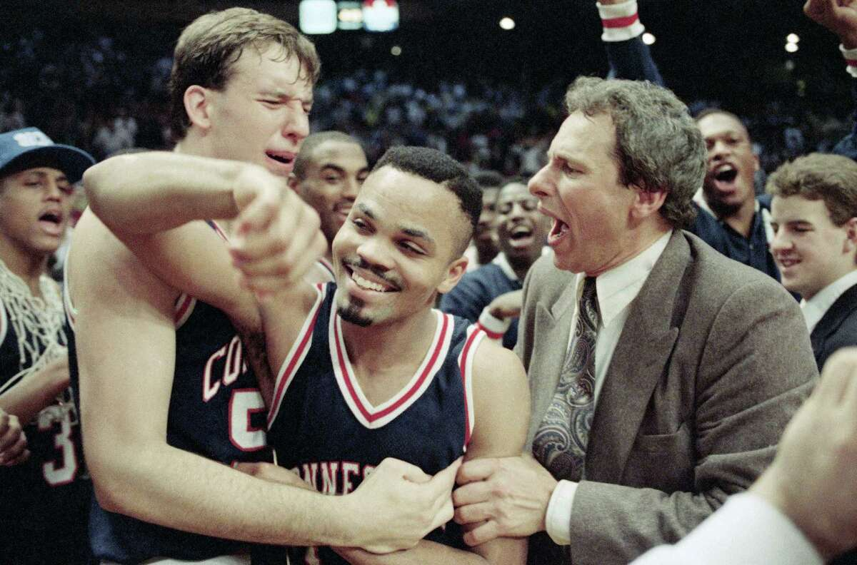 University of Connecticuts Dan Cyrulik, left, Chris Smith, center, and assistant coach Howie Dickeman rejoice after defeating Syracuse University 78-75in Big East action, Sunday, March 11, 1990, New York. Smith won the Most Outstanding Player award in the tournament. (AP Photo/Gerald Herbert)