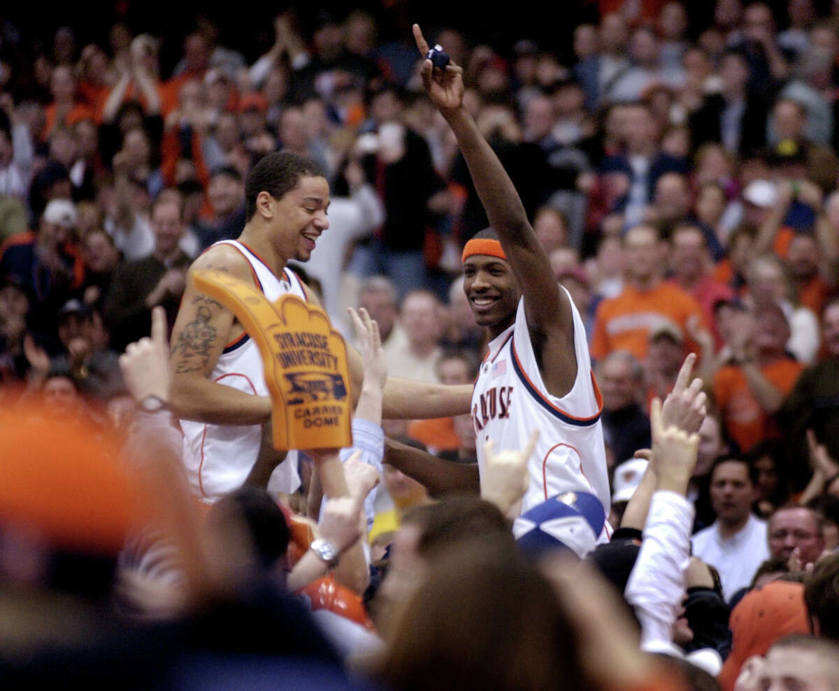 Syracuse's Terrence Roberts, left, and Hakim Warrick celebrate a 67-56 win over Connecticut with fans in Syracuse, N.Y., Sunday March 7, 2004.
