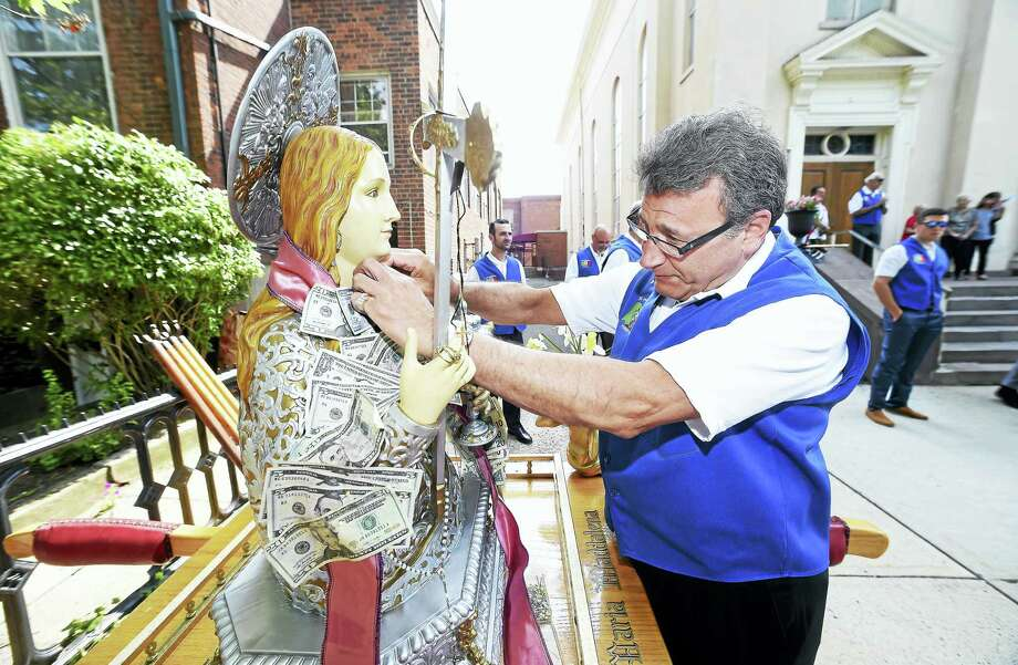 Joe Savo of New Haven pins a donation onto the statue of Santa Maria Maddalena, the patron saint of Atrani, Italy, in front of St. Michael's Church before a procession through the Wooster Square neighborhood. Photo: Arnold Gold / Hearst Connecticut Media