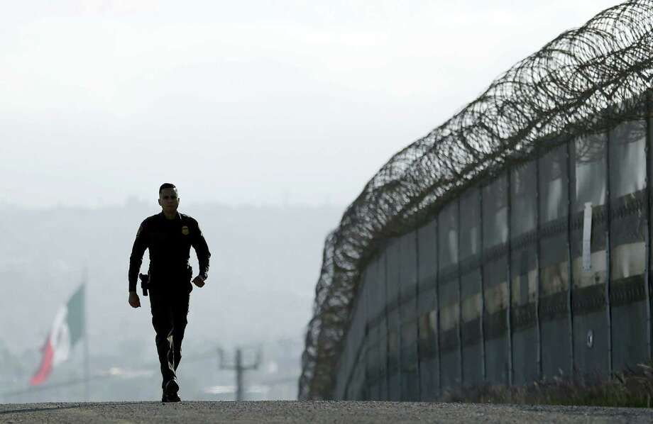Gregory Bull / associated press   Border Patrol agent Eduardo Olmos walks near the secondary fence separating Tijuana, Mexico, background, and San Diego in San Diego. Photo: AP / Copyright 2016 The Associated Press. All rights reserved. This material may not be published, broadcast, rewritten or redistribu