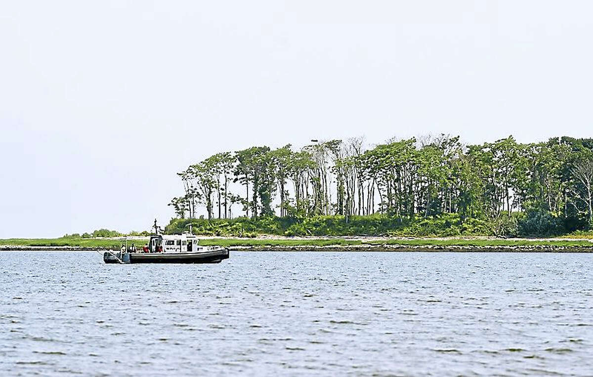 A boat searches for a man swept off a sandbar in Long Island Sound off Milford on Friday.