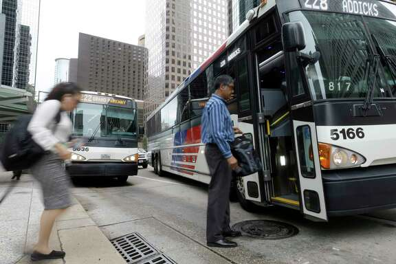 Commuters board a Metro bus at Louisiana and McKinney in Houston.