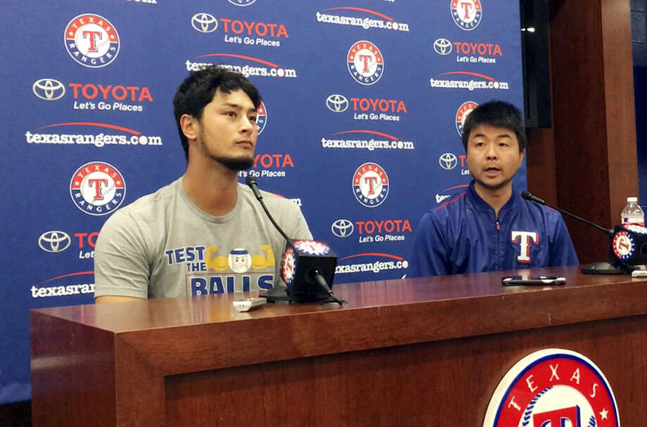 Pitcher Yu Darvish, left, responds to a question with help from his translator Hideaki Sato during a news conference regarding his trade to the Los Angeles Dodgers on Monday. Photo: The Associated Press   / Copyright 2017 The Associated Press. All rights reserved.