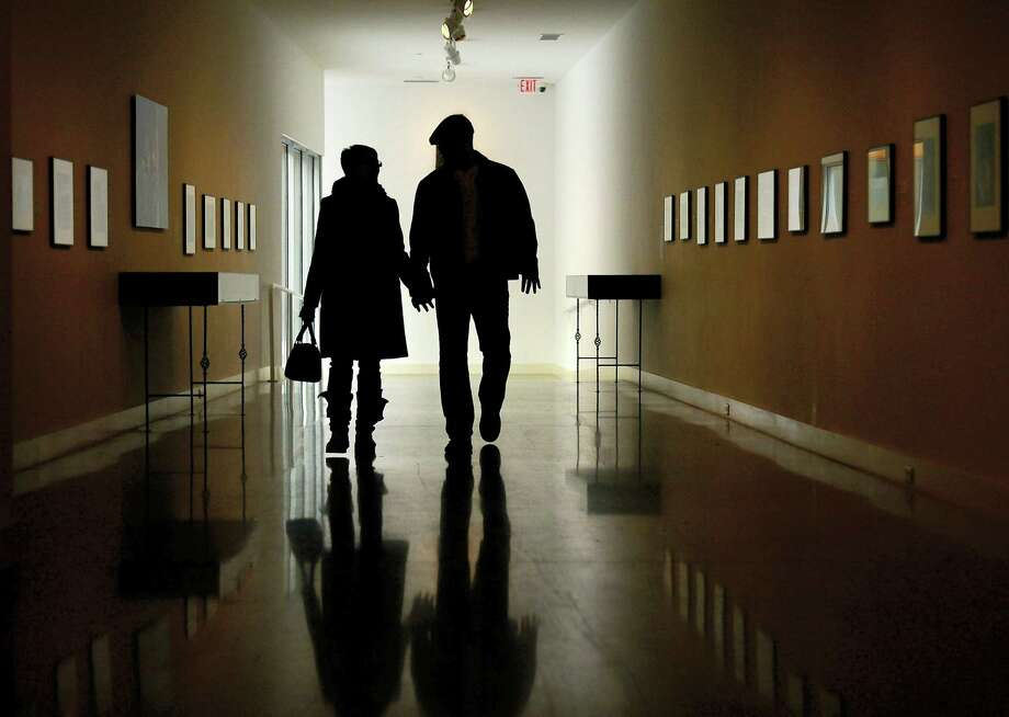 A couple walks down the Bacon Gallery at the Erie Art Museum, in Erie, Pa. Photo: Jarid A. Barringer / Erie Times-News Via AP, File   / Erie Times-News