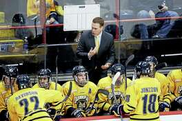 Quinnipiac head coach Rand Pecknold talks to players on the bench.