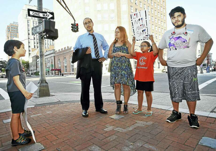 """Javier """"Javi"""" Hsu, 6, of Hamden attends a rally on the New Haven Green fighting the deportation of Nury Chavarria, Wednesday, July 19, 2017. Hsu's maternal grandparents emigrated from Cuba. Chavarria is pictured with her attorney, Glenn Formica and two of her four children, her oldest, Elvin Martinez, 21, who has a learning problem and impaired motor skills due to cerebral palsy and her youngest child, Hayley Chavarria, 9.  (Catherine Avalone – Hearst Connecticut Media) Photo: Catherine Avalone/New Haven... / Catherine Avalone/New Haven Register"""