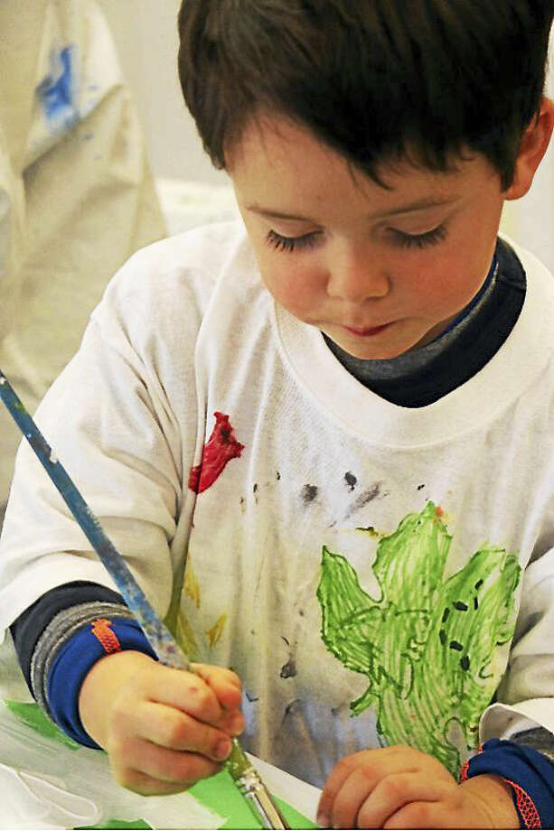 A child artist concentrates at the art center. Photo: Photo Courtesy Of GAC