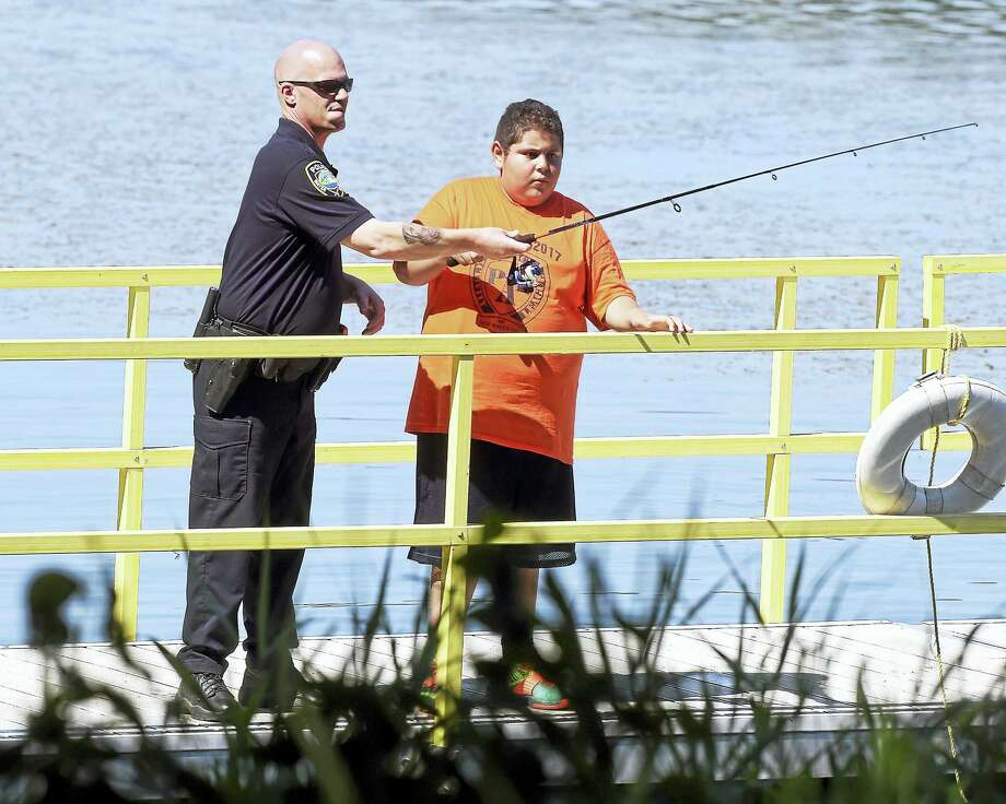 Regional Water Authority Police Officer Paul Ruggiero, left, assists Angel Rodriguez, 13, of New Haven with casting at Lake Saltonstall Monday in Branford. Photo: Arnold Gold / Hearst Connecticut Media