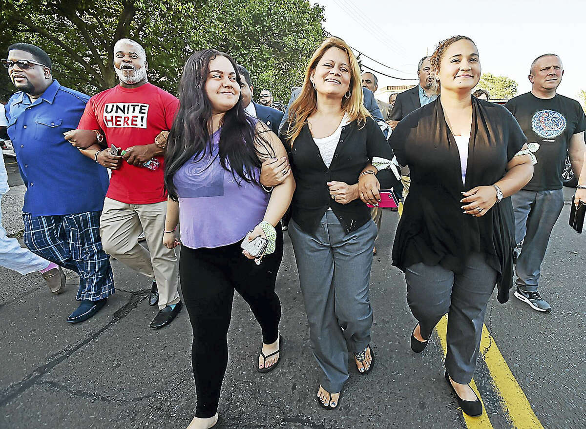Lindsay Chavarria, 18, third from left, looks at her mother, Nury Chavarria, center, as they and Diane Otero lead a march down South Front Street in New Haven Wednesday.
