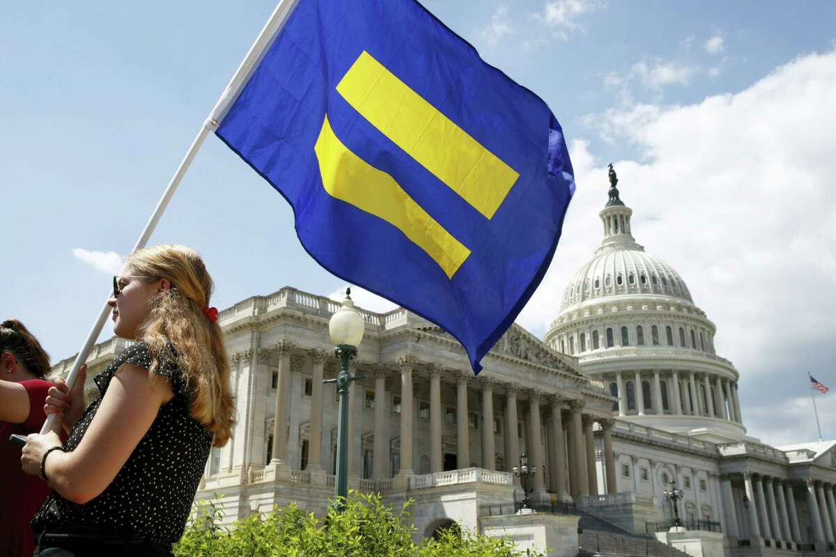 """A supporter of LGBT rights holds up an """"equality flag"""" on Capitol Hill in Washington, Wednesday, July 26, 2017, during an event held by Rep. Joe Kennedy, D-Mass. in support of transgender members of the, in response to President Donald Trump's declaration that he wants transgender people barred from serving in the U.S. military """"in any capacity,"""" citing """"tremendous medical costs and disruption."""""""
