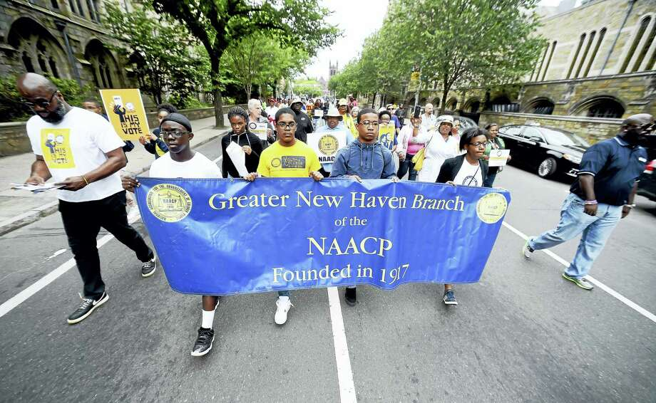 Left to right, Marquis McFadden, 14, Kaleb Walton, 17, Julian Brown and Kiara Brown, 18, of New Haven carry the NAACP banner to lead a Silent Protest Parade by the Greater New Haven Branch of the NAACP down Elm Street on the way to the New Haven Green for a rally on Saturday. Photo: Arnold Gold / Hearst Connecticut Media